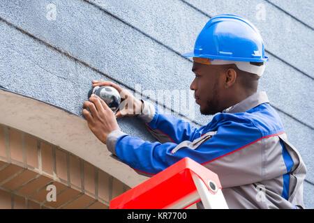 Il tecnico di installare la telecamera sulla parete Foto Stock