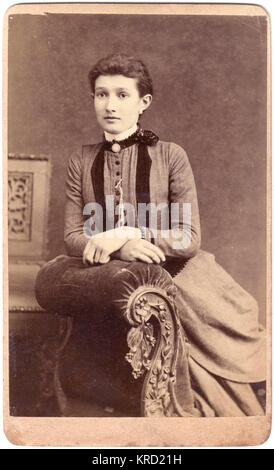 Una giovane donna vittoriana pone per la sua foto in studio, seduto su un ornato chaise longue. Indossa un abito con un colletto alto e i tasti sulla parte anteriore. Data: circa 1890s Foto Stock