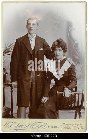 Una giovane coppia vittoriano rappresentano per loro fotografia in studio. Che indossano i loro abiti migliori, forse per un matrimonio. Indossa una lunga tunica, un gilet e un'ala collare con cravatta. Indossa un abito scuro con lacy decorazioni in bianco al collo e polsi e sul corpetto. Data: circa 1890s Foto Stock
