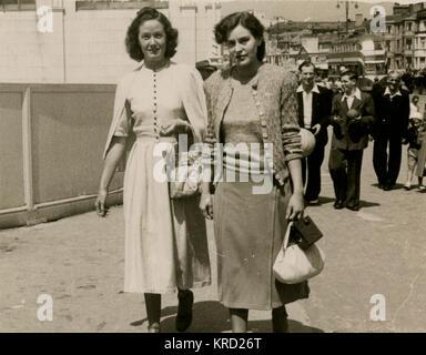 Due amiche a piedi lungo la strada mentre è in vacanza a Blackpool, Lancashire. Data: primi anni cinquanta