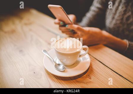 Le mani di close-up di una giovane e bella ragazza utilizza,tipi di testo su un telefono cellulare a un tavolo di Foto Stock
