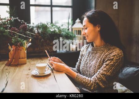 Bella ragazza giovane utilizza, tipi di testo su un telefono cellulare a un tavolo di legno vicino alla finestra Foto Stock