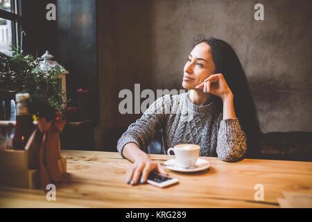 Giovane e bella ragazza beve caffè da una tazza di bianco, accanto al suo telefono cellulare in una caffetteria Foto Stock