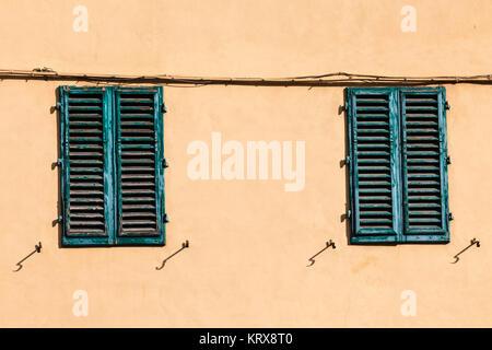 Chiuso verde di windows sulla parete gialla della vecchia casa Foto Stock