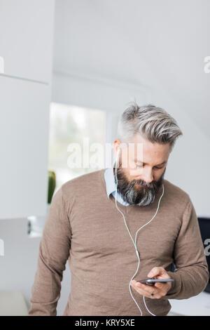 Un uomo con auricolari in ascolto per il suo telefono cellulare Foto Stock