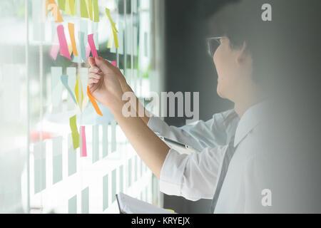 Imprenditore di mettere le sue idee sulla carta nota una presentazione in sala conferenze. La messa a fuoco in mani Foto Stock