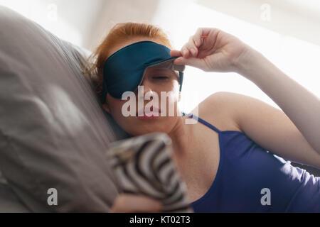 Giovane donna con maschera di sospensione di svegliarvi in bed and snoozing sveglia sul telefono cellulare, telefono Foto Stock