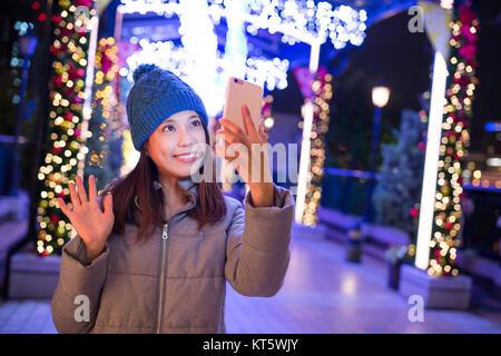 Donna prendendo selfie dal telefono cellulare con il natale decorazione presso ngiht