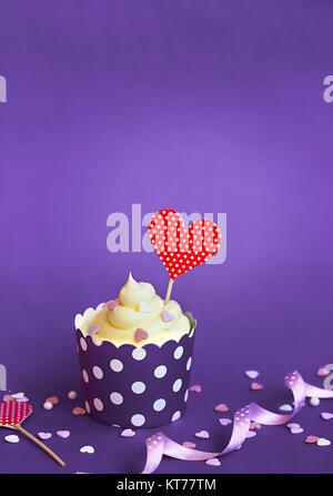La vaniglia tortina con piccoli cuori decorativi e cuore rosso topper, in viola la carta da forno cup, contro lo Foto Stock
