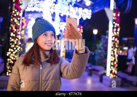 Donna prendendo selfie dal telefono cellulare con decorazioni di Natale