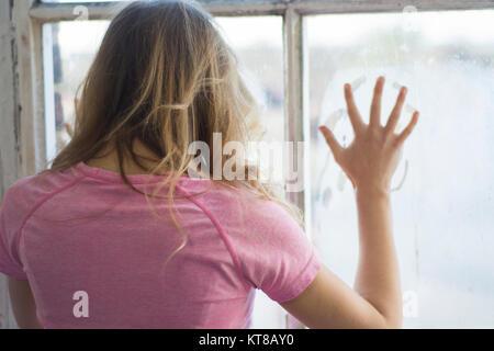 Vista posteriore di una donna bionda in piedi dalla finestra mani toccano il vetro Foto Stock