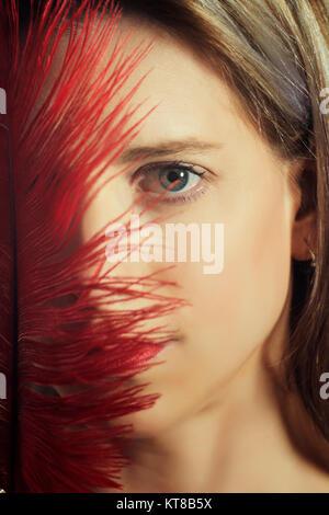 Close up ritratto di una donna bionda che nasconde il viso con ared giù Foto Stock