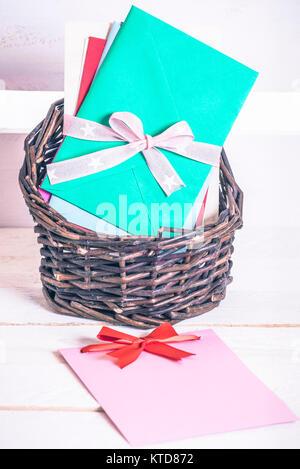 Cesto in Vimini piena di lettere multicolori legati insieme con nastro e un messaggio vuoto card con un fiocco rosso su bianco tavola di legno. Foto Stock
