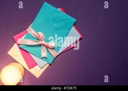 Mazzetto di lettere multicolori legati insieme con il nastro rosa e la prua e una candela accesa in loro prossimità, su un viola sullo sfondo di legno. Foto Stock