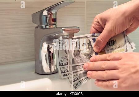 Il riciclaggio di denaro nel lavandino. ragazzo lava i dollari sporchi sotto acqua corrente. Mani maschio tenendo un centinaio di dollari sotto l'acqua. 500 bucks