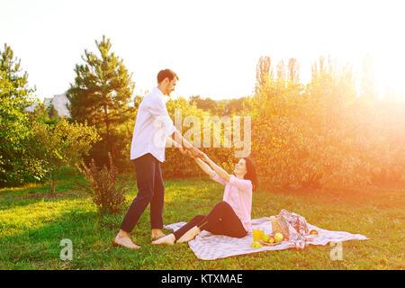 Felice coppia incinta nel parco su picnik Foto Stock