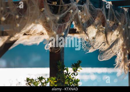Vecchio Tutina in rete appesa su una costruzione in legno al giorno soleggiato vicino al mare. Foto Stock