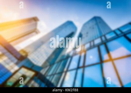 Abstract di sfocatura dello sfondo bokeh immagine di grattacieli moderni nel nuovo quartiere degli affari in bella luce della sera al tramonto con lens flare effetto filtro Foto Stock