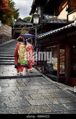 Due Maiko, Geisha apprendisti in splendidi kimono colorati con lunghi intricato obi a piedi con un ombrellone su Foto Stock