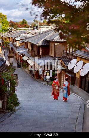 Due Maiko, Geisha apprendisti in variopinti kimono in piedi su una vecchia strada Yasaka dori in Kyoto, nei pressi Foto Stock