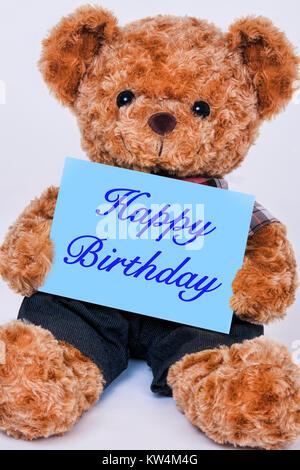 Simpatico orsacchiotto tenendo un cartello blu che legge Buon Compleanno isolato su uno sfondo bianco Foto Stock