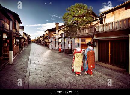 Due Maiko, Geisha apprendisti in splendidi kimono colorati con obi lunghe passeggiate lungo vuoto Hanamikoji Dori Foto Stock
