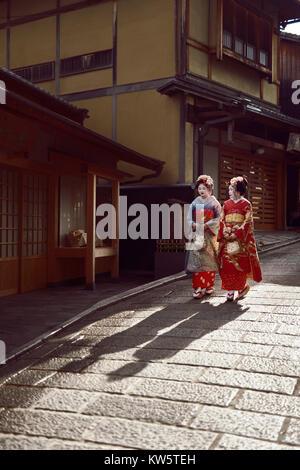 Due giovani Maiko, Geisha apprendisti in bright kimono camminando verso il basso su una vecchia strada di Higashiyama, Foto Stock