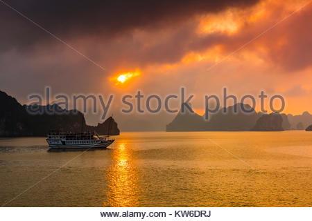 Tramonto a Halong Bay, Vietnam del Nord. Il bay offre 3.000 di calcare e dolomite formazioni carsiche e le isolette Foto Stock