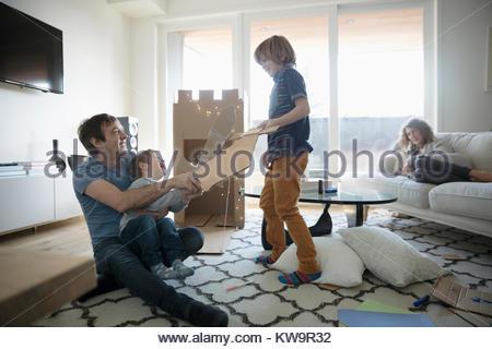 Guardare la madre padre e figli giocare con le spade di cartone in salotto Foto Stock