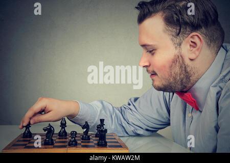 Giovane uomo chunky concentrata sulla strategia di costruzione mentre gioca a scacchi. Foto Stock