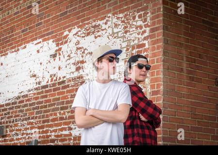 Due giovani uomini che indossano occhiali da sole e cappelli in piedi di schiena con le braccia incrociate rustico contro un muro di mattoni in città Foto Stock