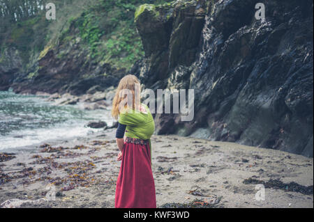 Una giovane madre è sulla spiaggia con il suo bambino in una imbracatura Foto Stock