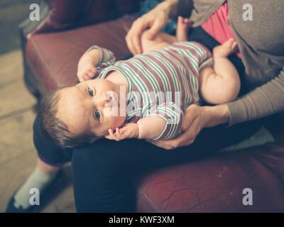 Un bambino felice sul grembo di sua madre a casa Foto Stock