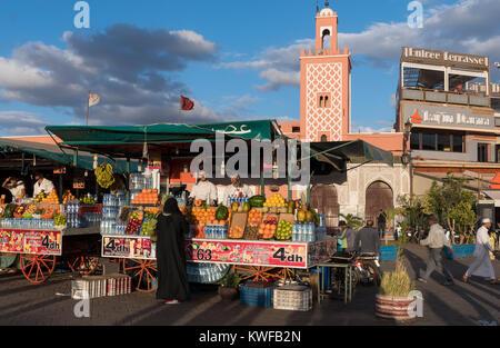 Scena di strada con la gente e la luce drammatica in piazza Jemaa el Fna, la piazza. Foto Stock