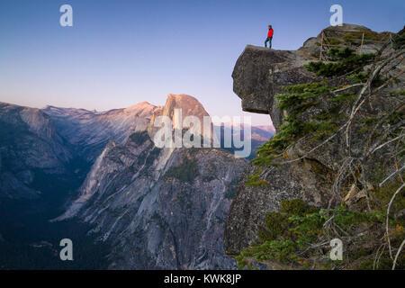 Un intrepido escursionista è in piedi su una roccia a strapiombo guardando verso il famoso Half Dome al punto ghiacciaio al tramonto, il Parco Nazionale Yosemite in California