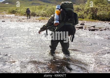 Gli escursionisti a piedi nel fiume Foto Stock