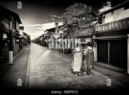 Bianco e nero scenario di due Maiko, Geisha apprendisti in splendidi kimono colorati con obi lunghe passeggiate Foto Stock