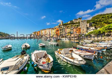 Una giornata di sole nel golfo di La Spezia con le barche nel porto e turisti che si godono il borgo marinaro di Foto Stock