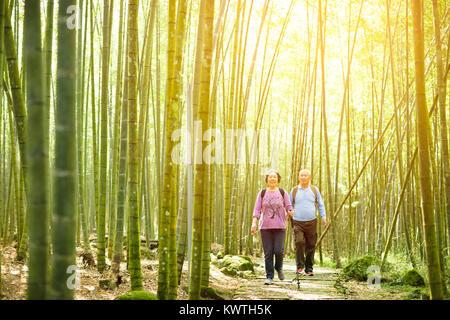 Coppia senior escursioni nel verde della foresta di bamboo Foto Stock