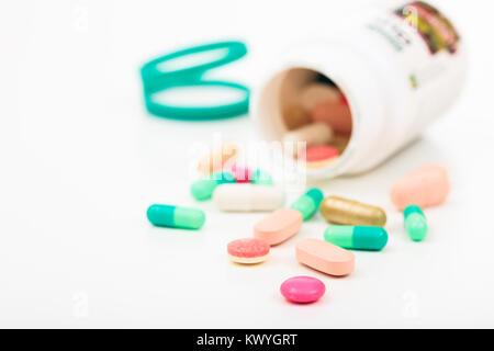 Pillole al di fuori di un bottiglia su sfondo bianco Foto Stock
