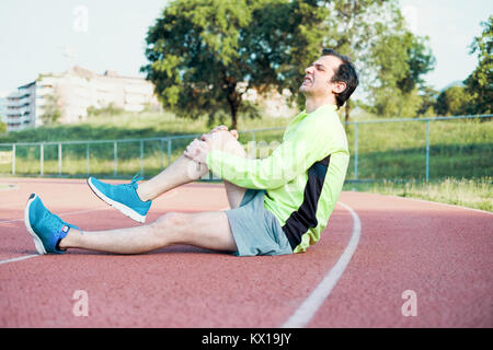 Esecuzione di uno sportivo sentire dolore dopo avente il suo ginocchio infortunato Foto Stock