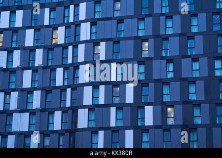 Incredibile immagine ravvicinata di edificio di appartamenti che mostra finestre blu con un leggero pannello blu Foto Stock
