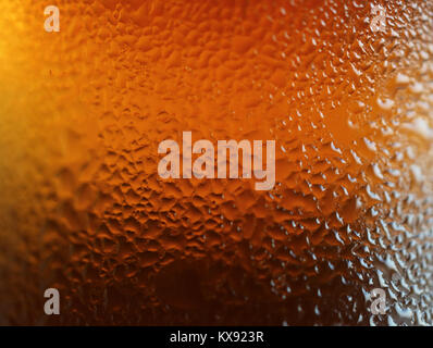 Macro shot di gocce di acqua sulla texture deep color arancione bottiglia, per sfondo astratto con il fuoco selettivo Foto Stock