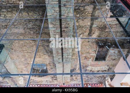 Guardando verso il basso attraverso un tetto di vetro, vedere la riflessione di un vecchio edificio in pietra, con Foto Stock