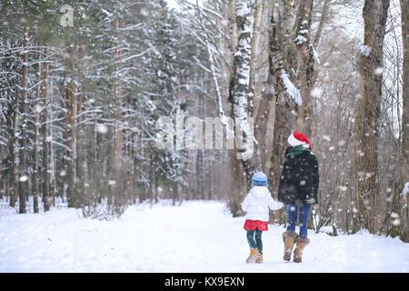 Una favola invernale, una giovane madre e figlia un giro in slitta Foto Stock