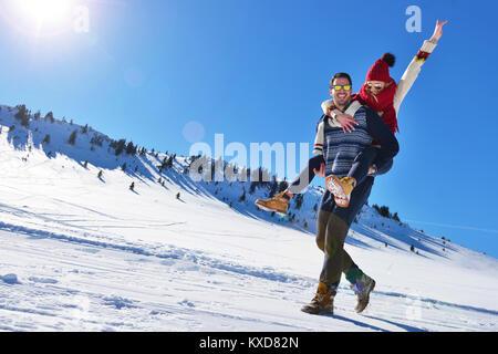 Coppia giovane divertirsi sulla neve. Felice l'uomo alla montagna dando piggyback ride per la sua ragazza sorridente. Foto Stock