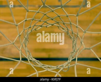 Vista attraverso il Basketball hoop. Guardando al pavimento tramite rete bianca in alto e in basso. Foto Stock