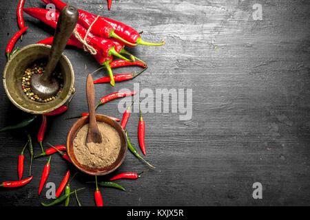 Grano di pepe caldo in un mortaio con un pestello. Sulla lavagna.