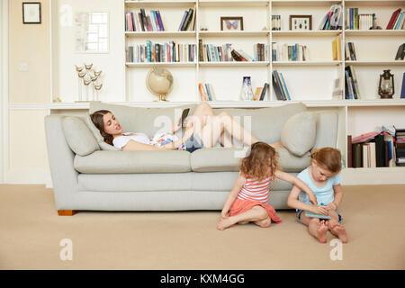 Donna incinta sdraiata su un divano con lo smartphone e le figlie seduta sul disegno del pavimento Foto Stock