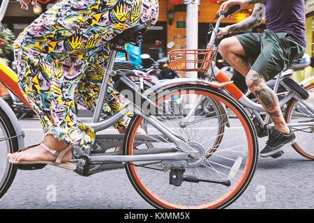 Vita scende vista multi etnico hipster giovane escursioni in bicicletta lungo la strada,Shanghai Concessione Francese,Shanghai, Foto Stock
